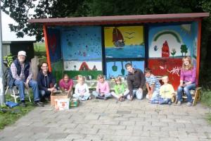 Das Bild zeigt die fertige Neudorfer Bushaltestelle mit den teilnehmenden Kindern sowie den Betreuern Heinz Holstein und Henning Bernau